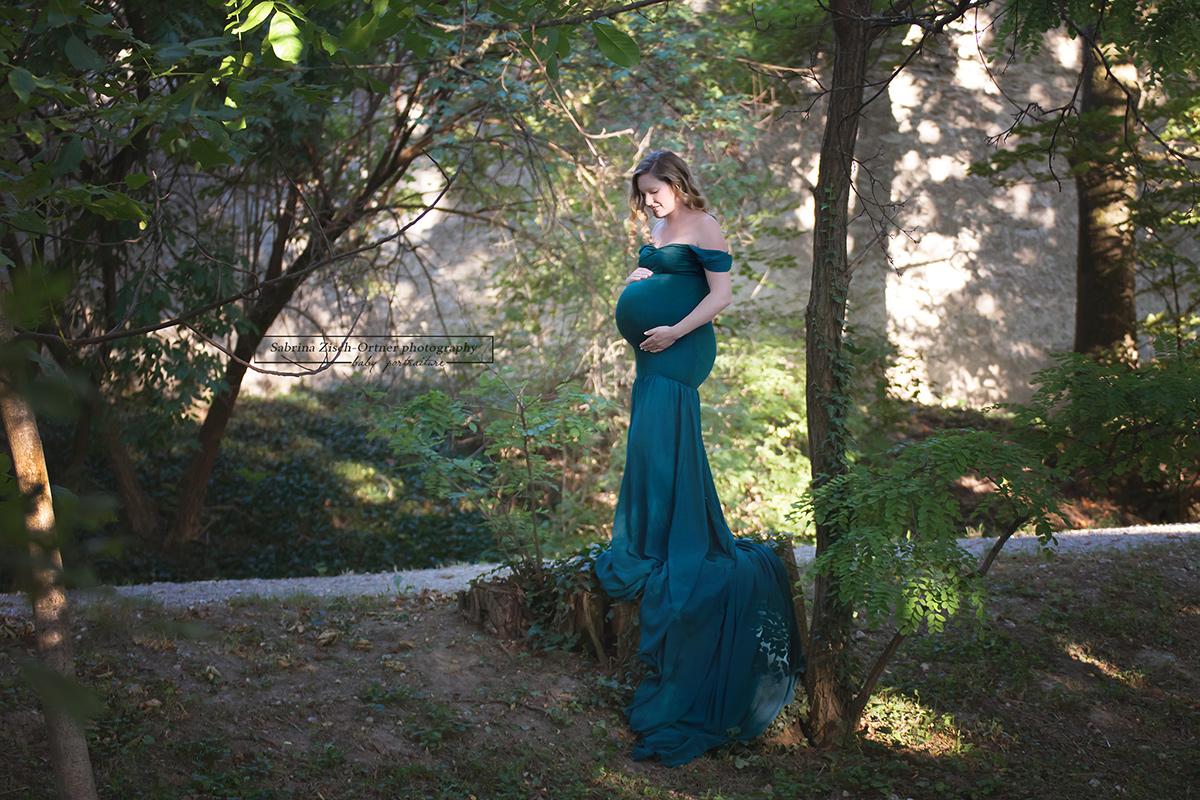 Schleppe des grünen Babybauchkleides im Waldstück in Szene gesetzt