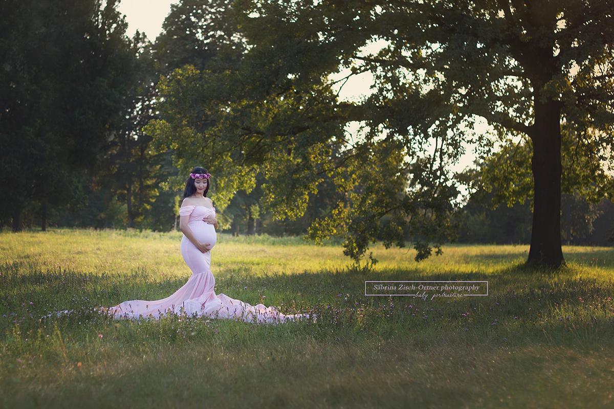 Schwangere im rosa Babybauchkleid im offenen weiten Park