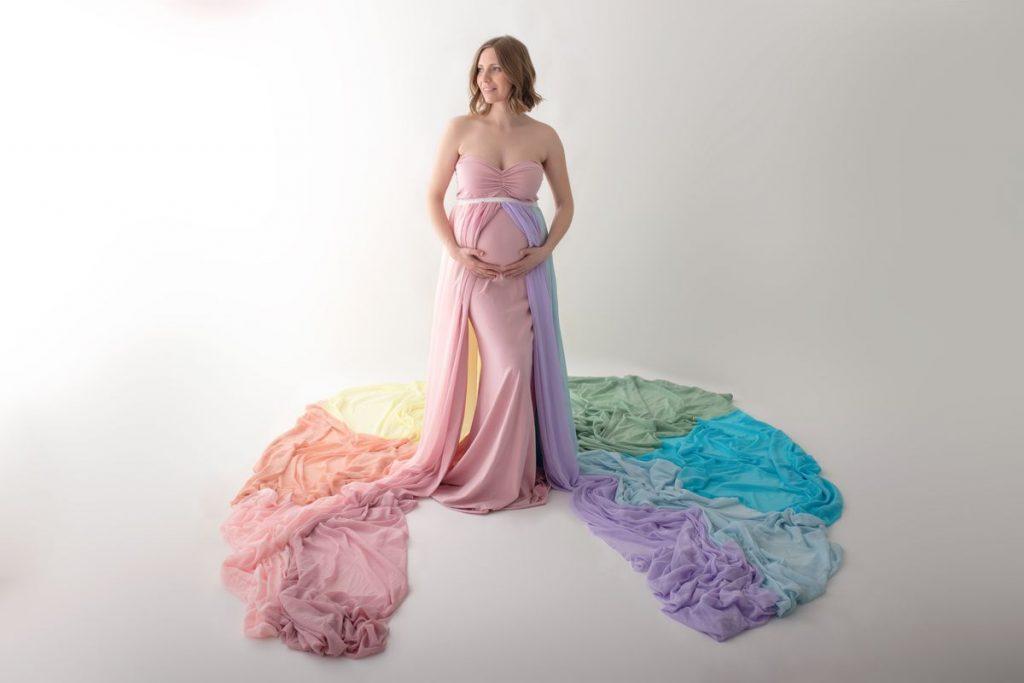 Babybauch im rosa Kleid mit Rock in pasteligen Regenbogenfarben beim Fotoshooting