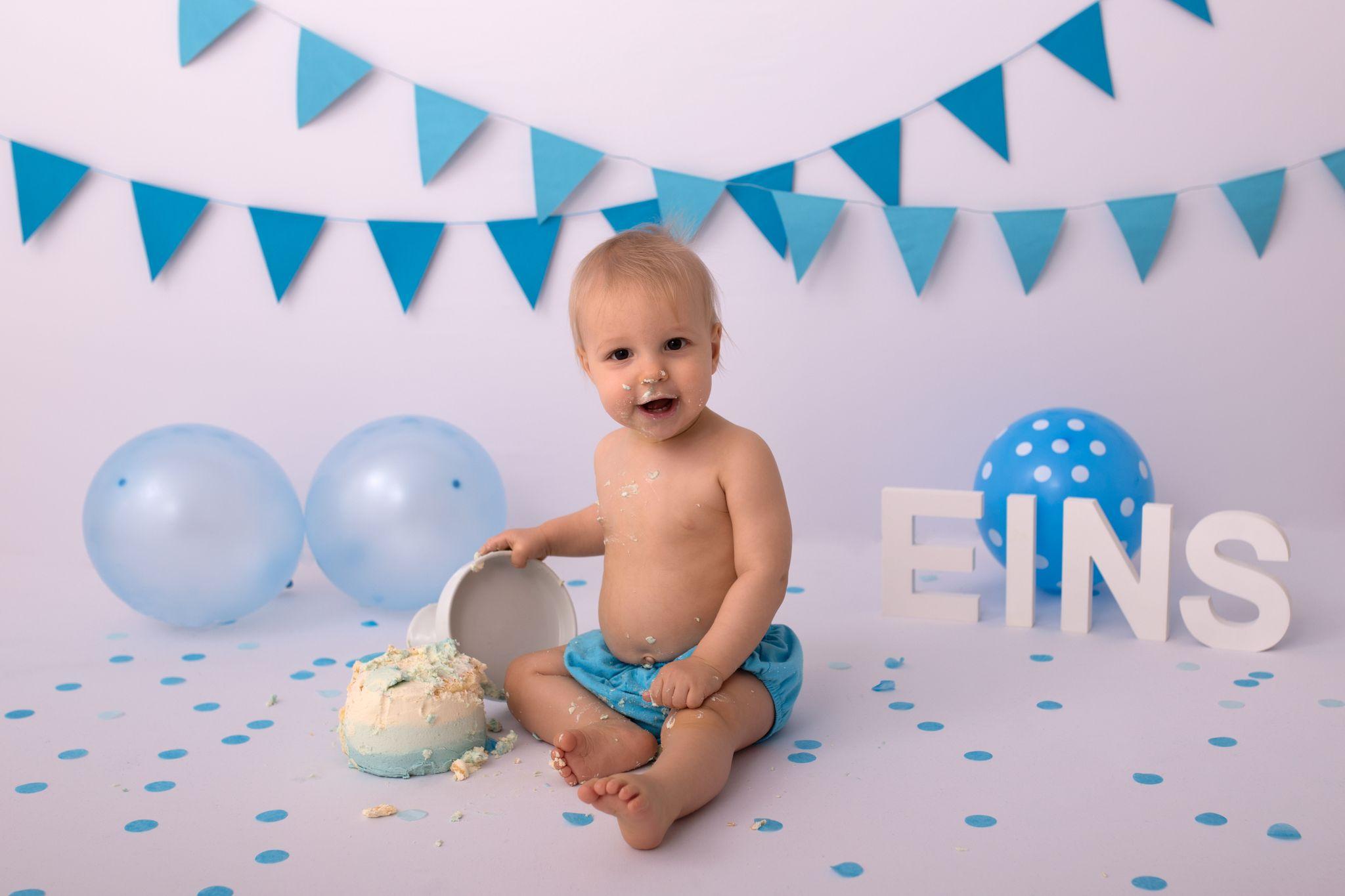ein lachendes mit Torte beklecktes Geburtstagskind zeigt sich auf dem Bild zum Cake Smash Portfolio