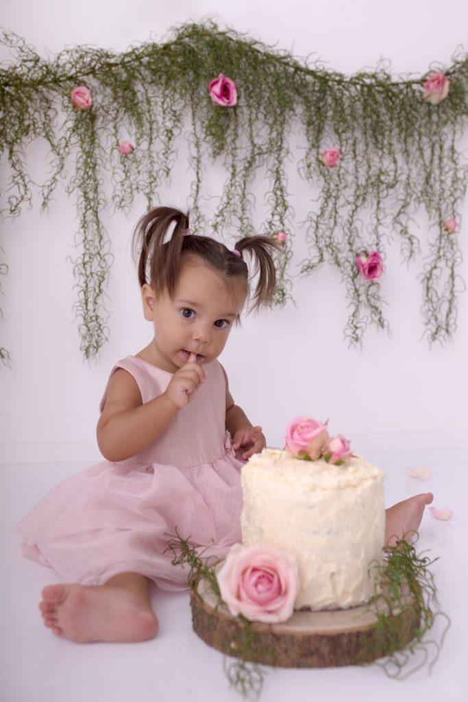 rosa Blumen schmücken den Hintergrund für das Cake Smash Geburtstagsshooting des kleinen Mädchens