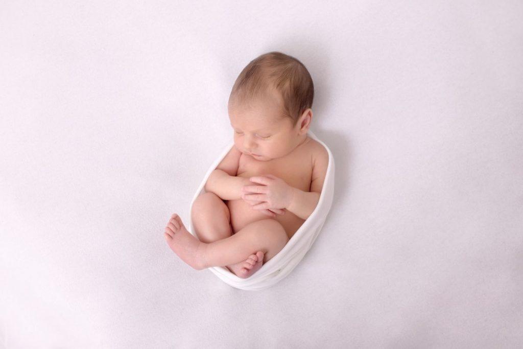 FAQ newborn baby Fotoshooting Wien und Umgebung zeigt ein schlafendes und gepucktes neugeborenes Baby