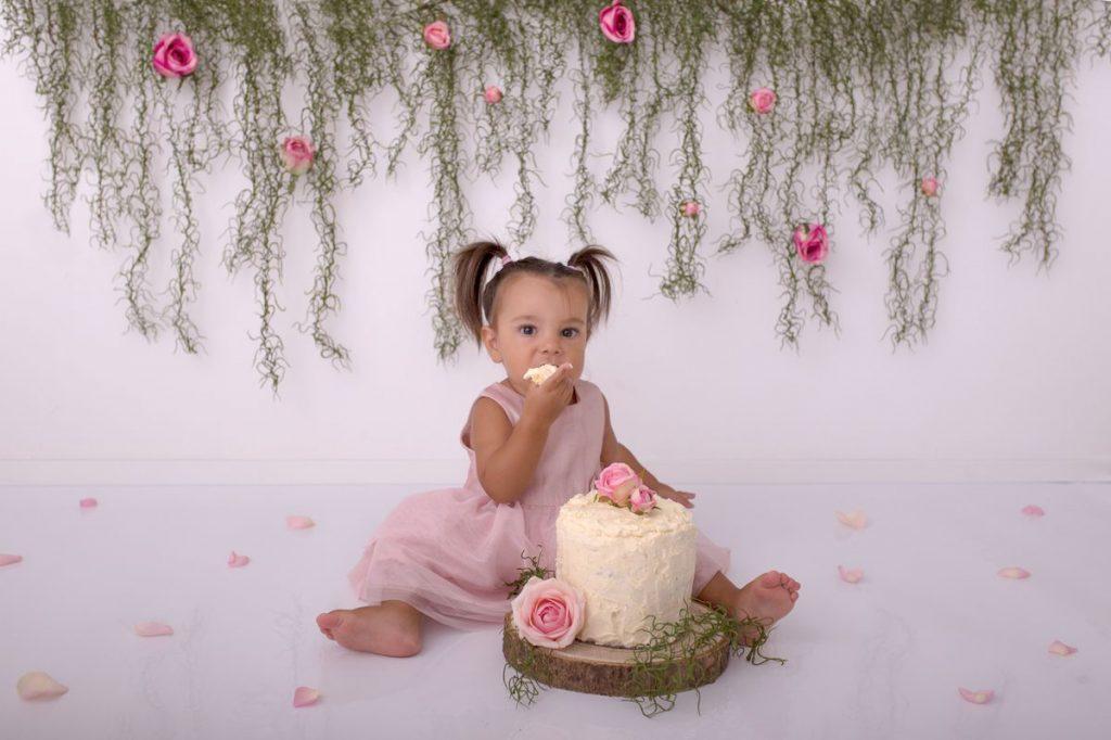 Geburtstagskind in ihrem rosa Kleid und vor Blumenhintergrund kostet von ihrer Cake Smash Fotoshooting Torte
