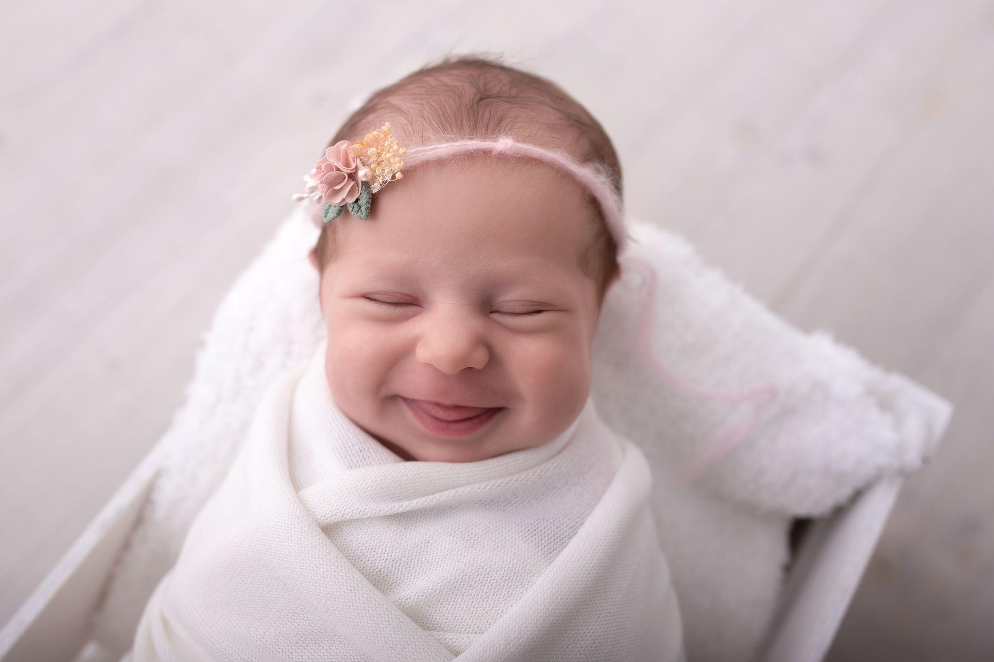 lächelndes kleines Neugeborenen Mädchen führt dich in die Produktwelt der Alben, Rahmen, Holzblöcke von Zisch-Ortner