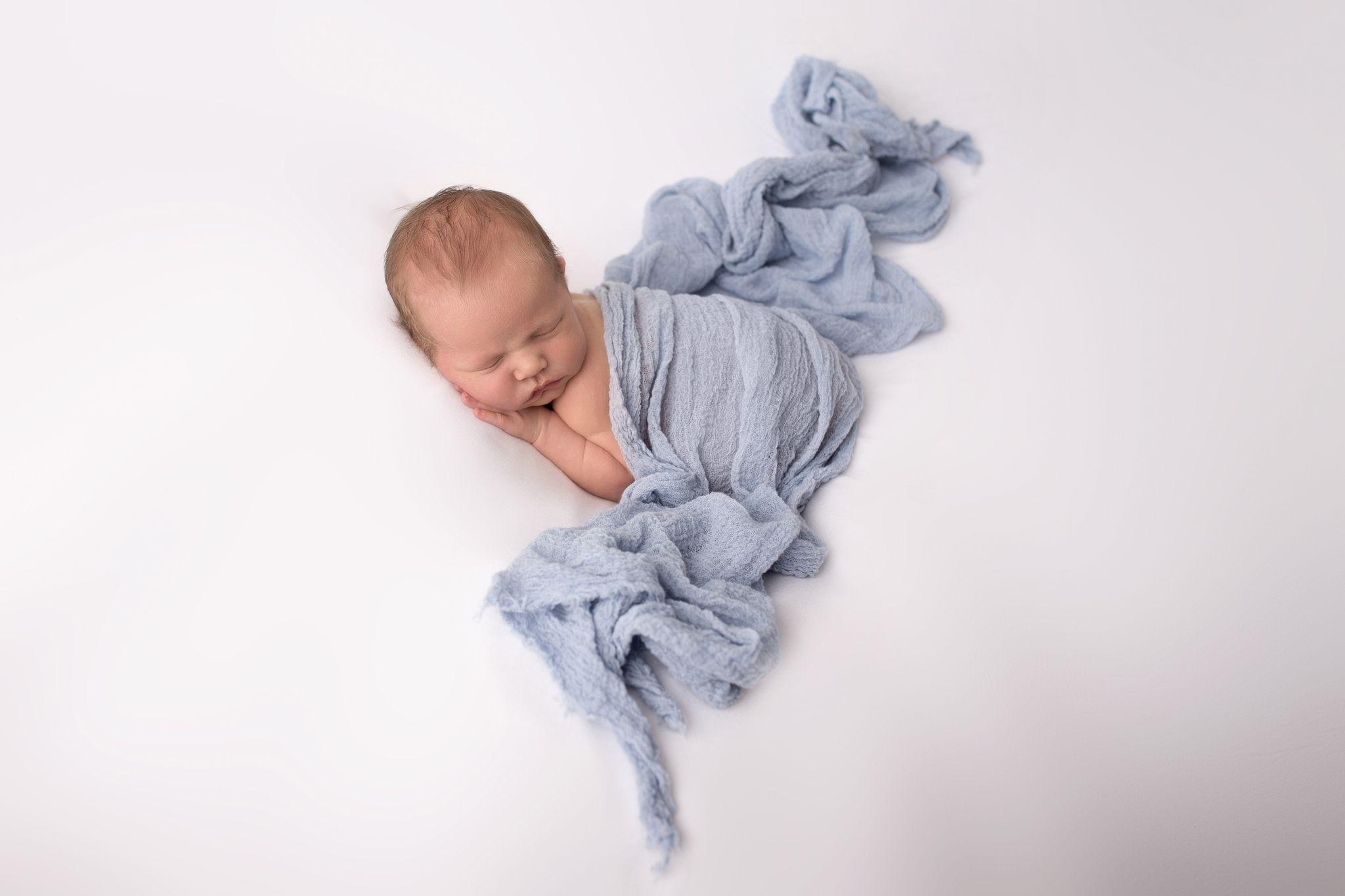neugeborener Bub in blauen Wrap führt euch zu Sabrina Zisch-Ortners Fotoshooting Angebot