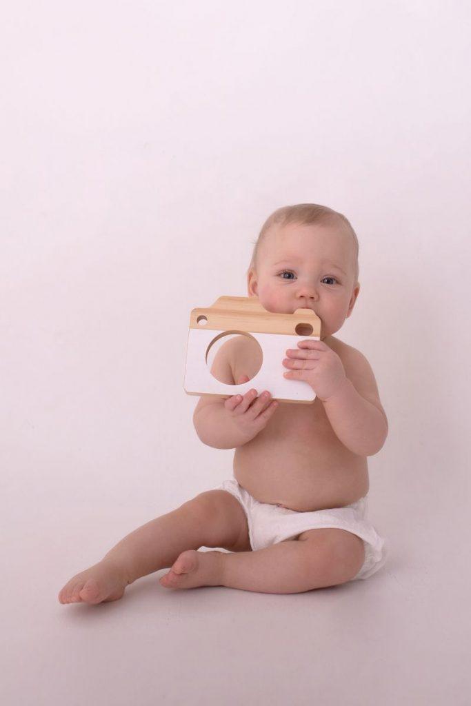 Meilensteinfoto welches kleinen 7 Monate alten Jungen mit einer Holzkamera zeigt
