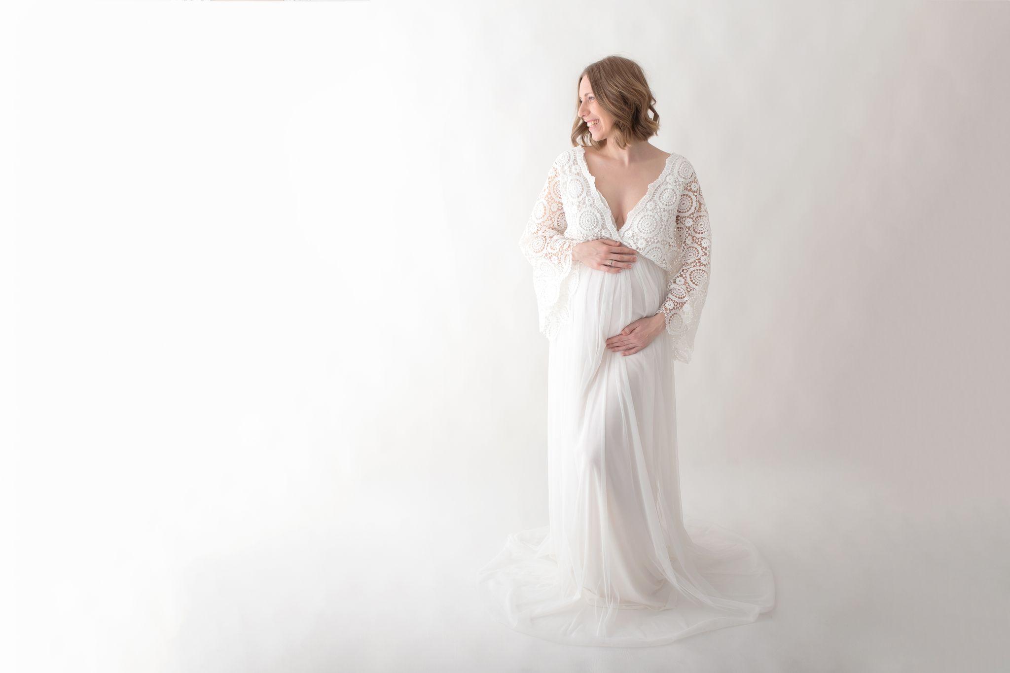 Schwangere im weißen handgeschneiderten Spitzen Babybauchkleid ziert das Titelbild der Fotoshooting Grundpreise