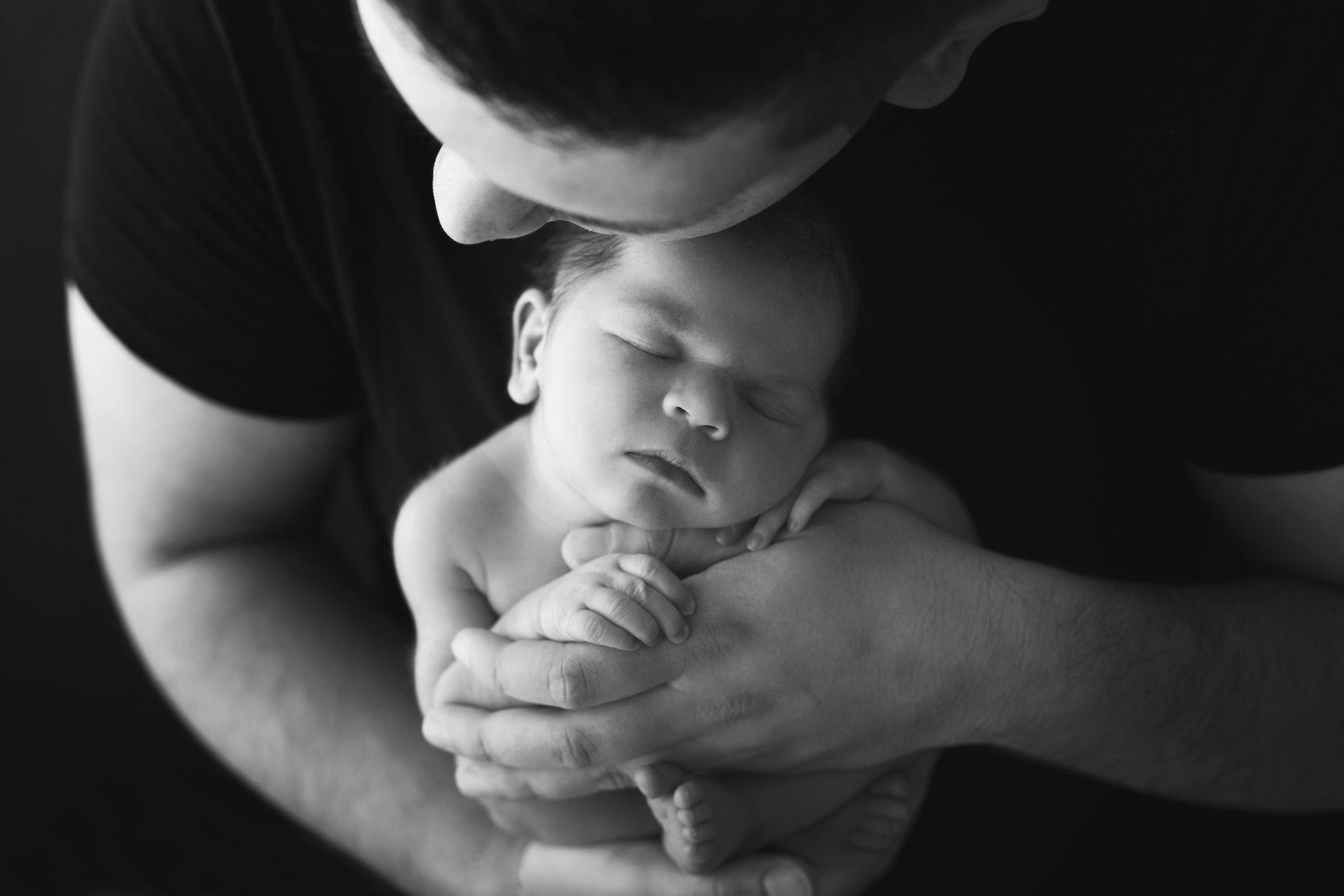 Papa und Tochter in kuschelnder schwarz weiß Pose beim Neugeborenen Shooting