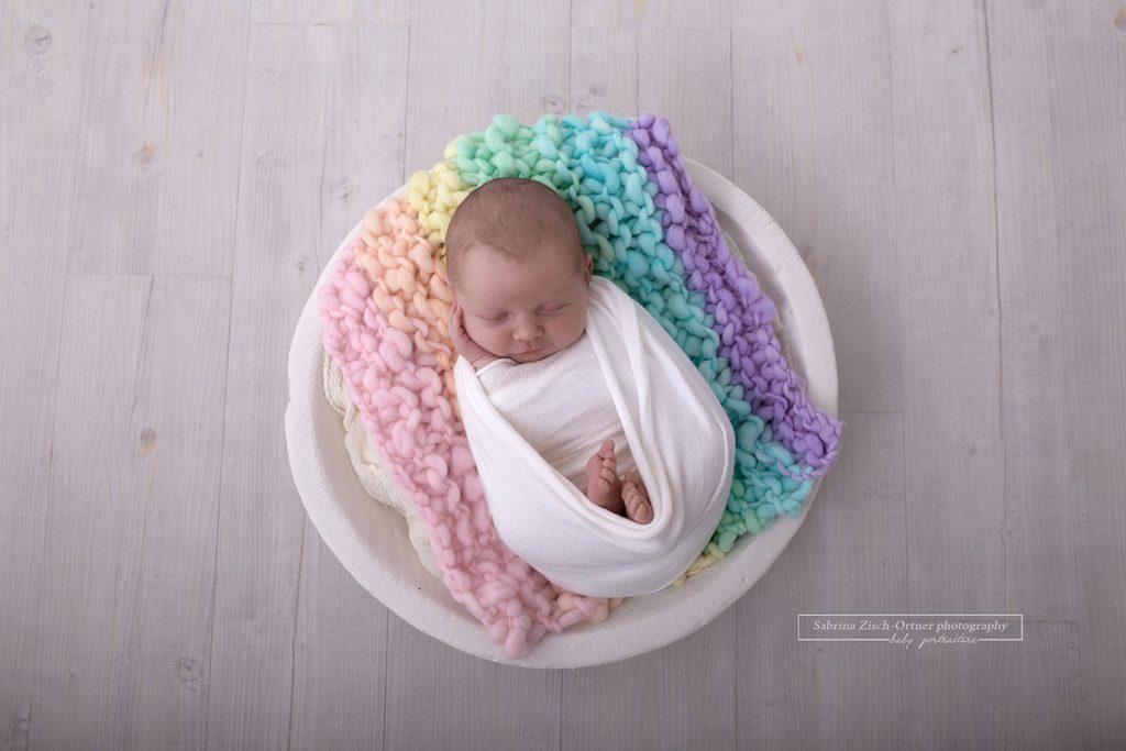 Baby auf Decke aus Regenbogenfarben in einer weissen Schalen