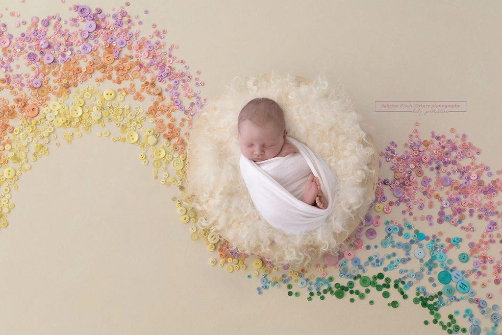 Baby in einem Regenbogen aus Knöpfen
