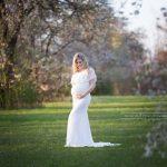 Bald Mama in weißem Babybauchkleid inmitten von weissen Blüten