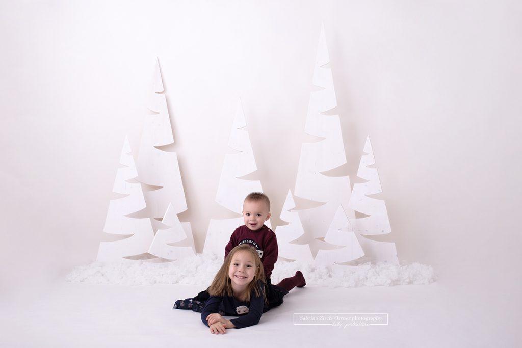 Bruder kniet auf seiner großen Schwester vor dem weißen weihnachtlichen selbstgemachten Baumhintergrund.
