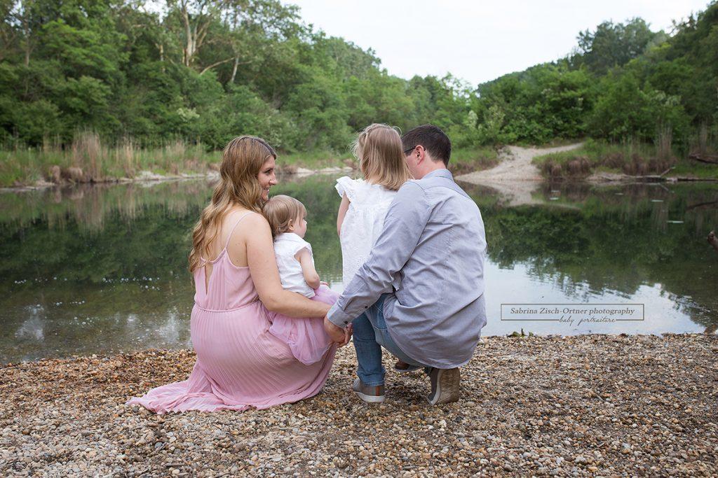 Die sich liebende Familie sitzend vor dem Wasser im Hintergrund wundervolles grün der Bäume
