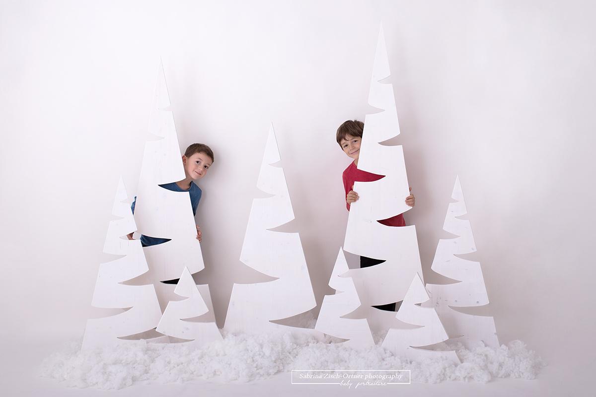 Ein Foto für Weihnachten bei welchem sich die zwei Burschen hinter den schlichten und weissen Weihnachtsbaeumen verstecken