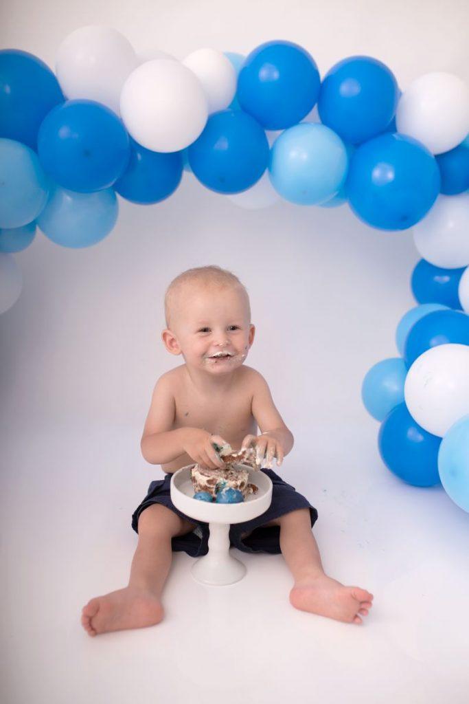 FAQ Cake Smash Shooting Zisch-Ortner Bild zeigt einen grinsenden mit Torte verschmierten 1 Jährigen