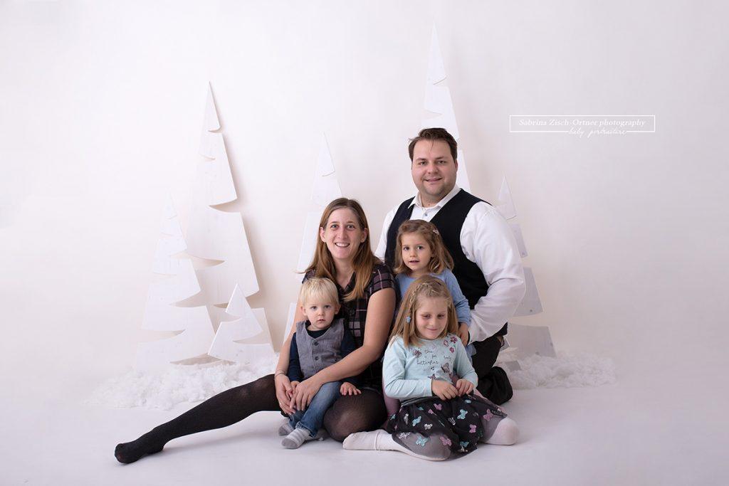 Familie mit 3 kleinen Kindern zu Besuch in meinem Studio in 1220 Wien für ein kuschelndes Familienfoto in meinem selbstgemachten weihnachtlichen Setup.