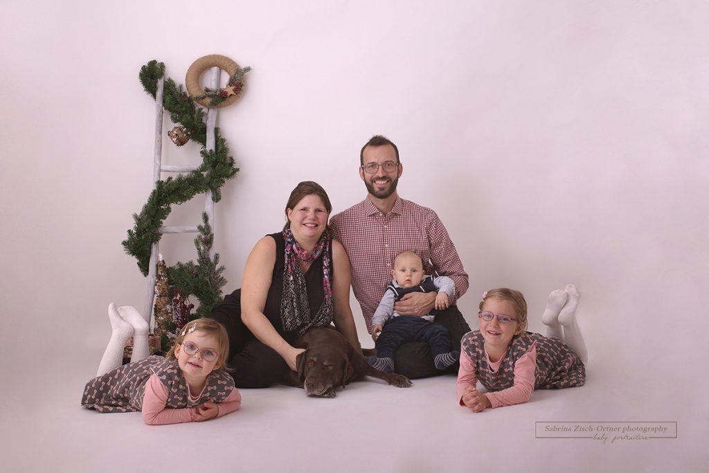 Fünfköpfige Familie mit Hund bei jährlichen Weihnachtsfotos