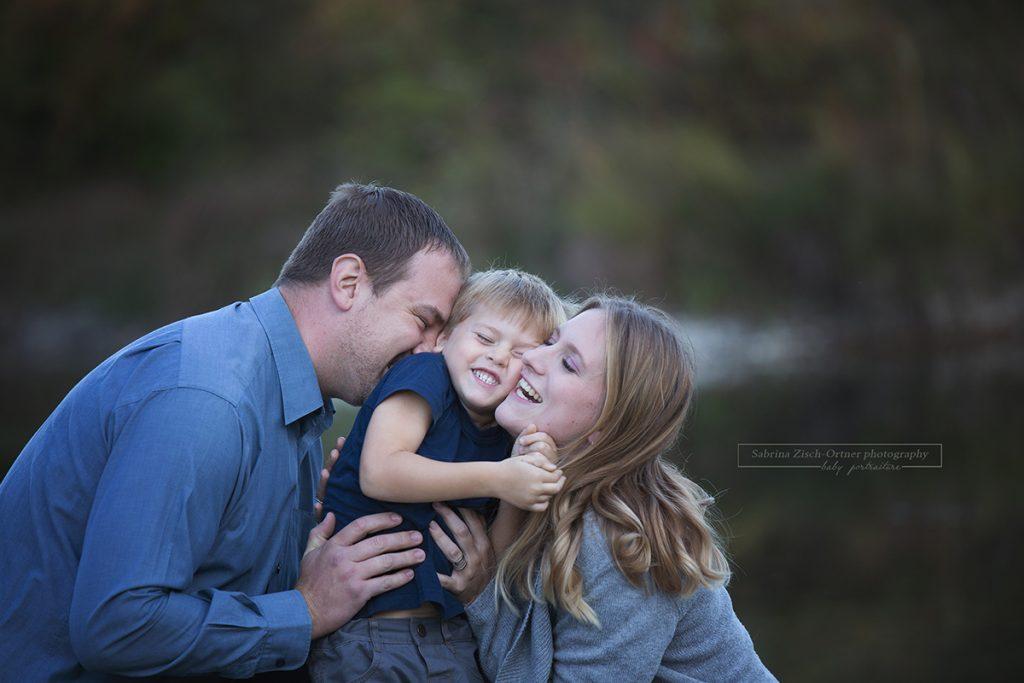 Familie zu Dritt bei einem lachenden Kitzel Foto