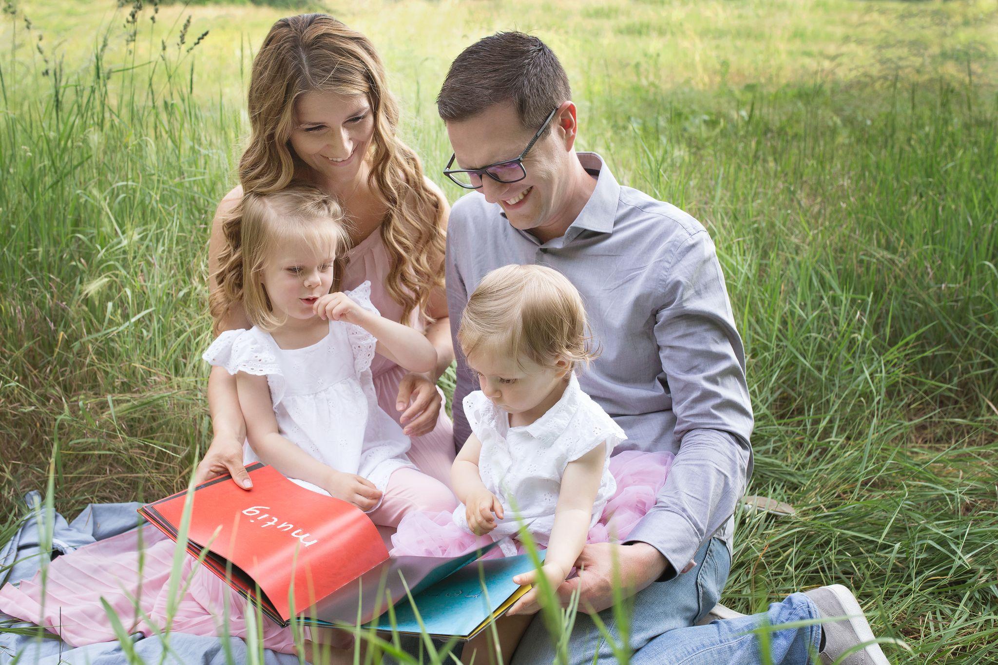 die lesende vierköpfige Familie in der Natur zeigt sich auf dem Titelbild der Familienshooting Galerie bzw. des Portfolios von Sabrina