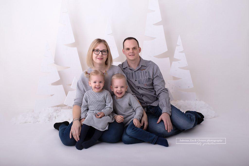 Das Familienfoto der süßen vierköpfigen Familie in grau gekleidet eignet sich perfekt als Weihnachtsgeschenk bzw. als Weihnachtskarte