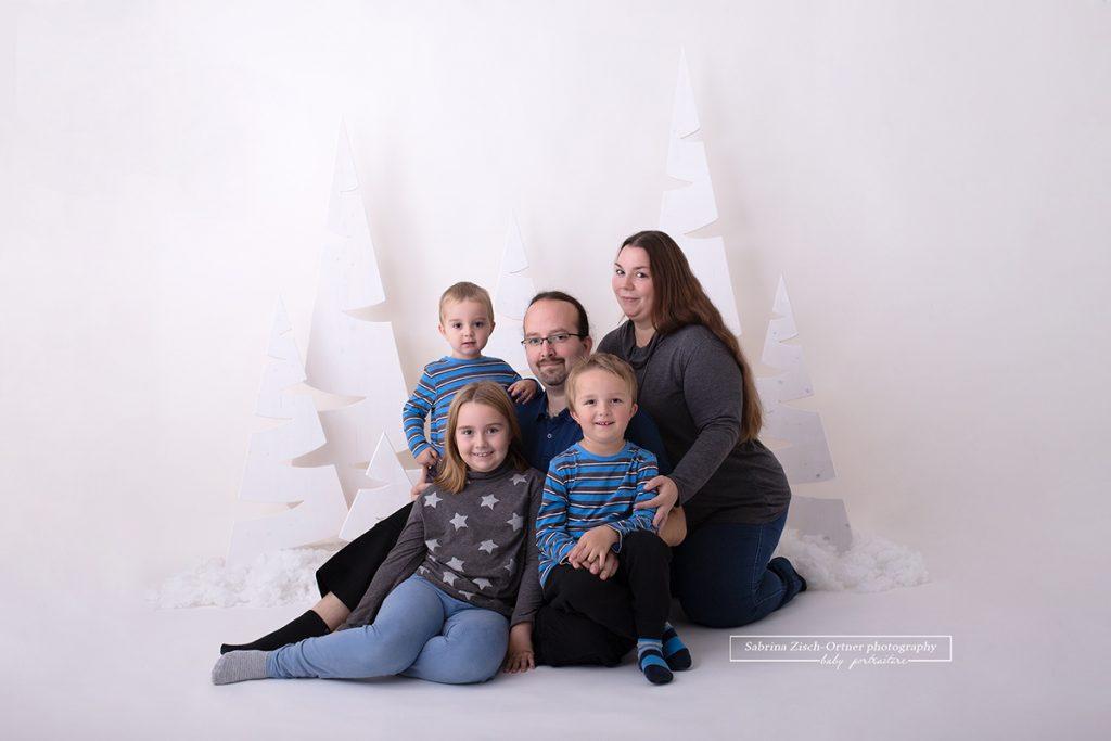 sitzendes und kuschelndes Familienfoto der fünfköpfigen Familie gemacht bei den Weihnachtsminisessions 2019