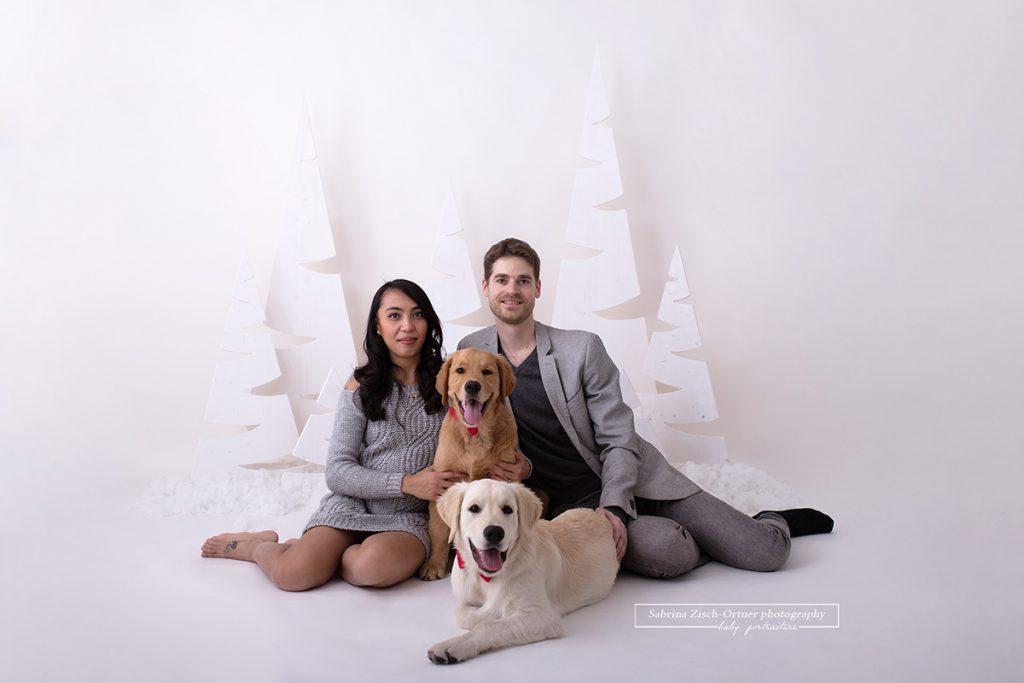 ein wunderschönes sitzendes Familienfoto welches die Herrchen mit ihren zwei Hunden, ihren Golden Retrievern, zeigt