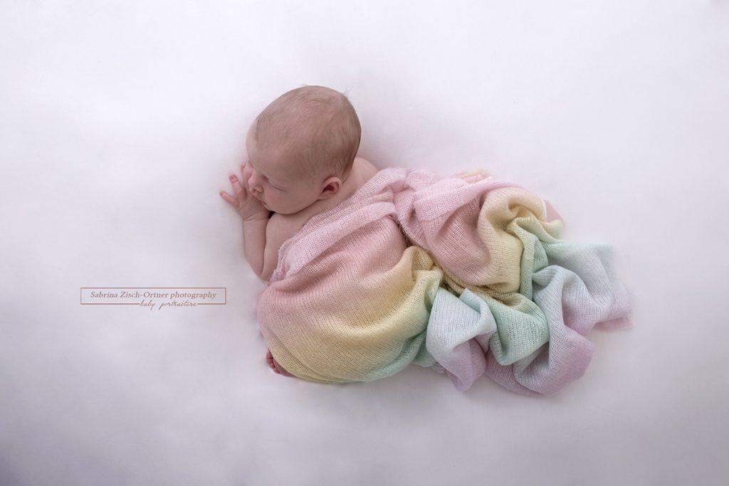 Foto von oben gemacht mit Blick auf Baby und Tuch in Regenbogenfarben