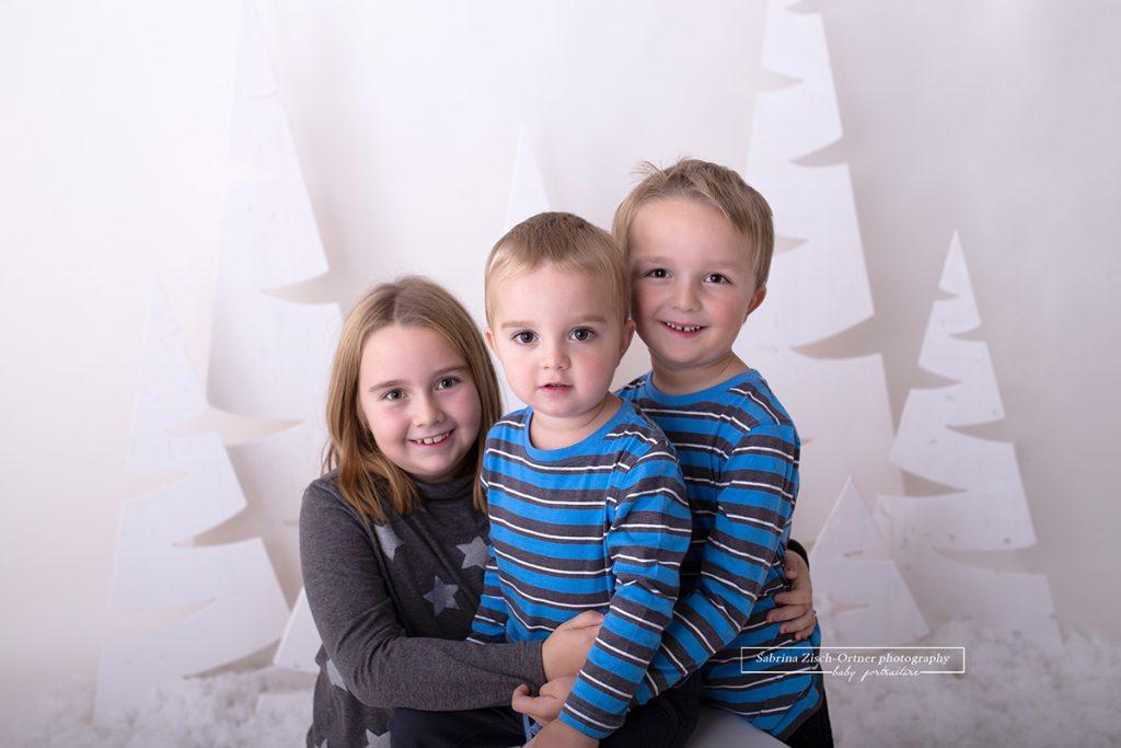 Geschwisterfotos, wie diese Nahaufnahme der drei, ist eine wunderschöne Erinnerung für die Eltern