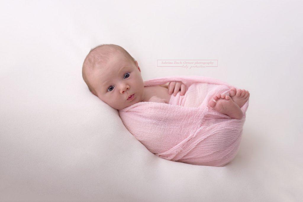 Grimassen schneiden eines neugeborenen Mädchens beim Fotoshooting