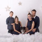 Weihnachtsfamilienfoto mit ihrem Hund in der Mitte