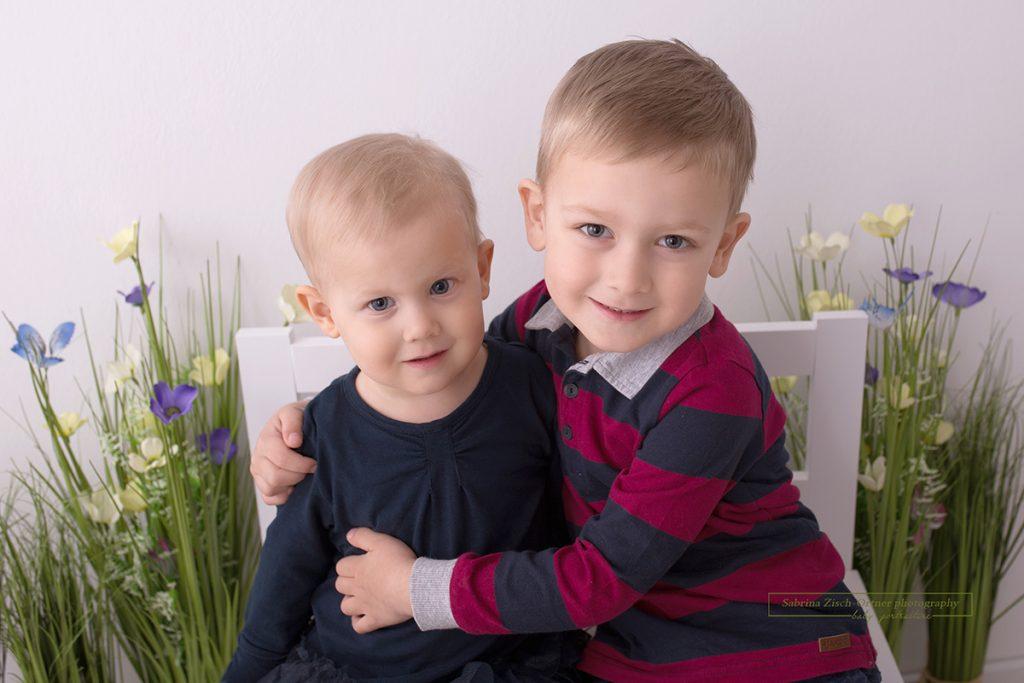 Lächelnde Geschwister in einem Frühlingssetup