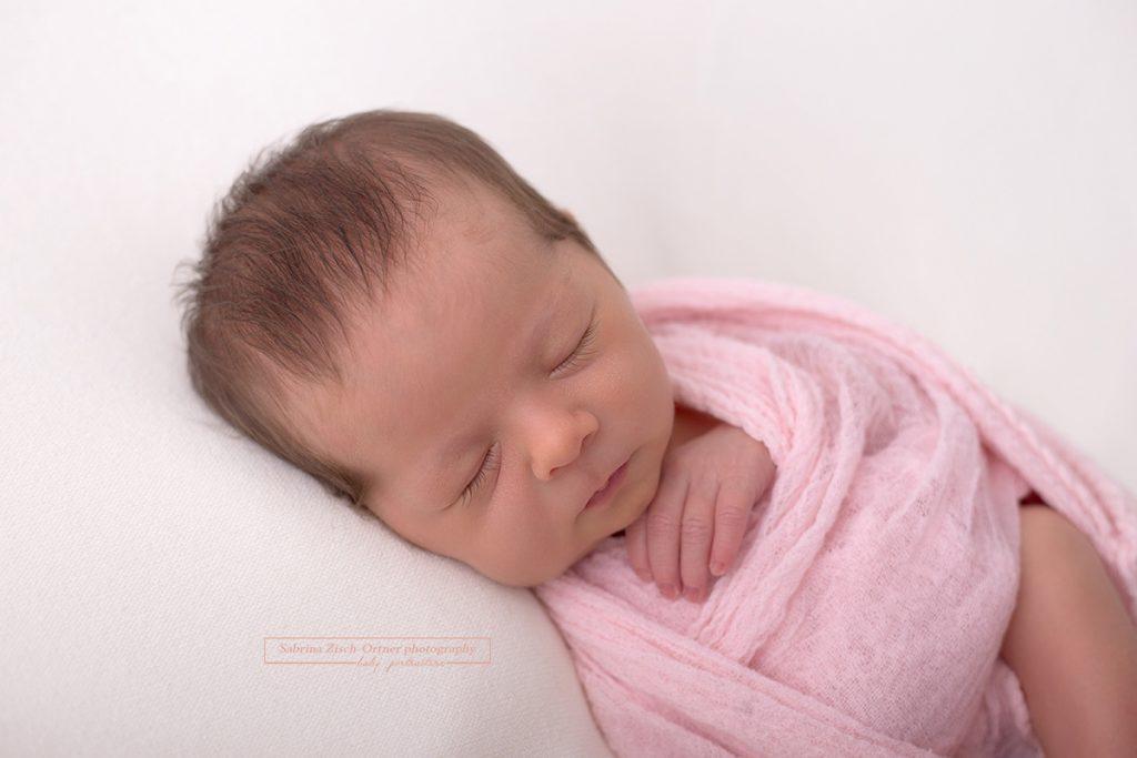 natürliches Portrait das Detail der Wrap Technik zeigt und ein wundervolles neugeborenes Mädchen
