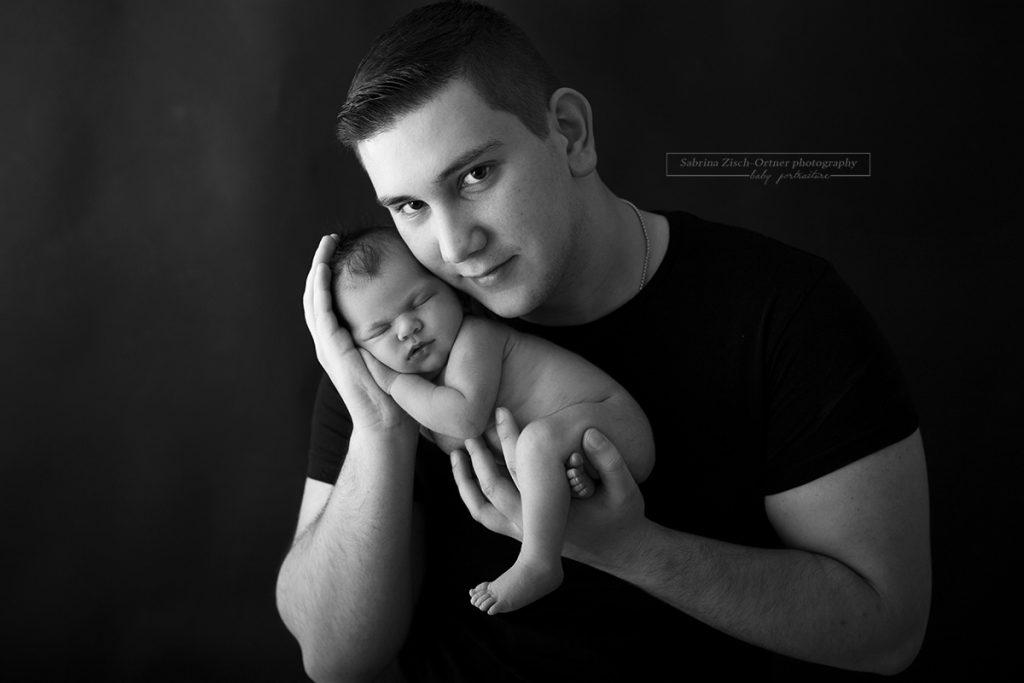 Papa hält seine neugeborene Tochter in seinen Händen