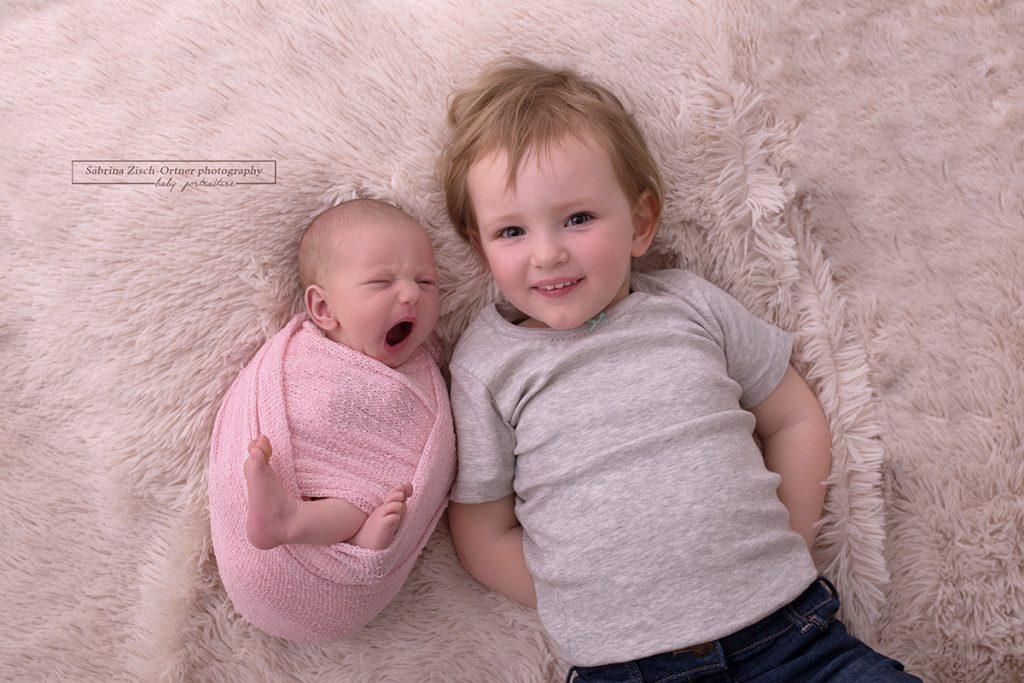 lächelndes Geschwisterfoto als Highlight bei einem Neugeborenen Fotoshooting