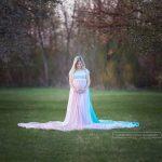 Schwangere im blauen Schwangerschaftskleid mit pastellfarbigen Regenbogenrock im Frühling