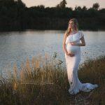 Schwangere im weißen Bellykleid vor mit Abendlicht getränktem Wasser