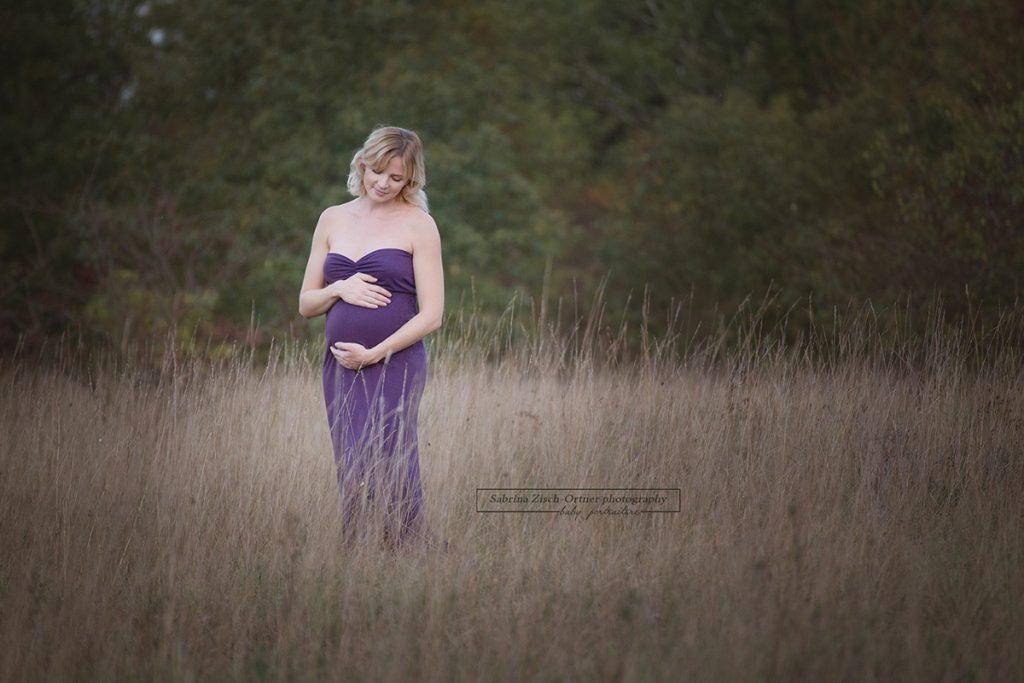 Schwangere mit Babybauchkugel im hohen Savannengras stehend