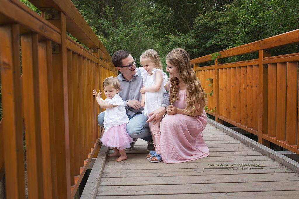 Wunderhübsches Familienfoto auf einer braunrötlichen Brücke
