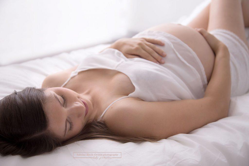 liegende Mama in weiß auf weißem Bett mit Babybauch