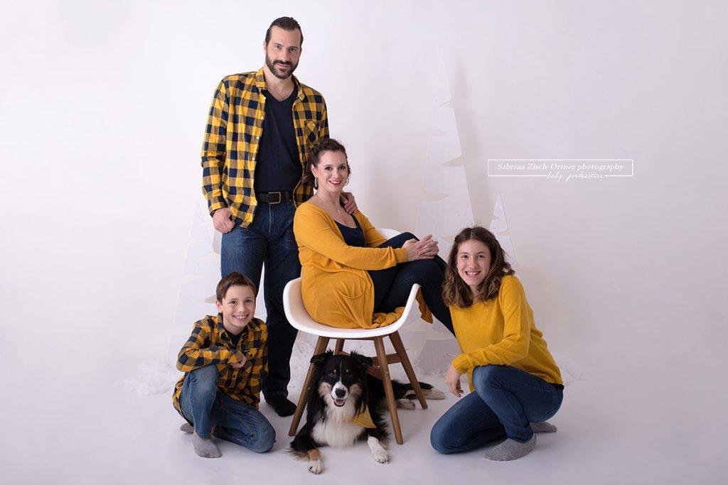 4 koepfige Familie mit Hund in gelb und blau gekleidet mit Sessel als Accessoire im weihnachtlichen Setup