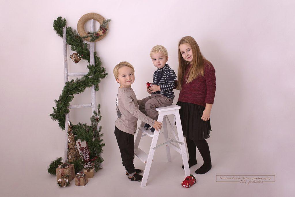 drei Geschwister lachen in die Kamera
