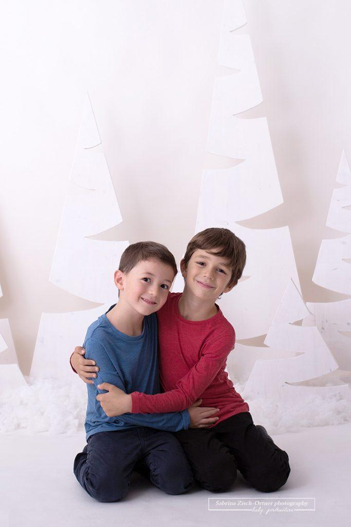 Brüder lächeln in die Kamera während sie sich zur Freude der Eltern herzlichen umarmen