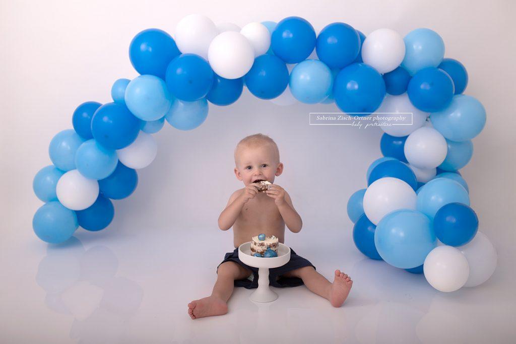 erste Biß in die leckere Cake Smash Torte mit ganz vielen Luftballons im Hintergrund