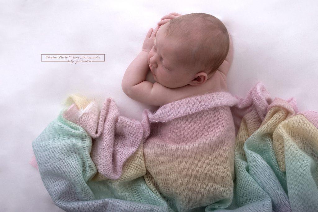 handgestrickte Decke in Regenbogenfarben über neugeborenen Kind