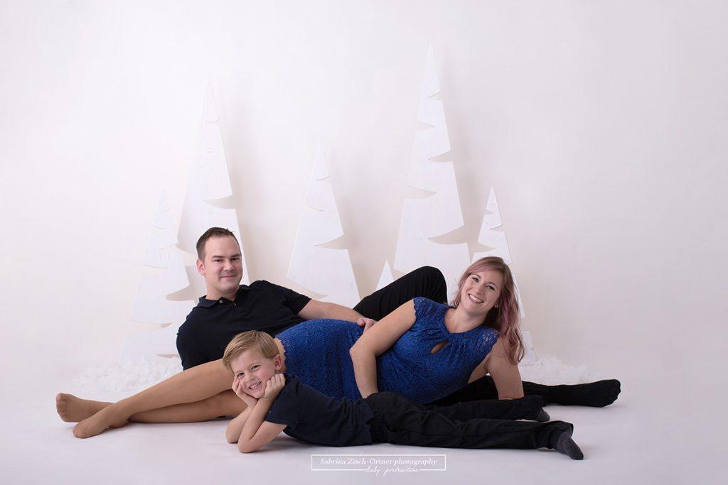 jährliche Familienfotos zu oder vor Weihnachten zeigen über die Jahre gesehen eine Erinnerung des größer Werdens die unser Gedächtnis gar nicht alle speichern kann. Wie dieses liegende Familienfoto von Mama, Papa und Sohn.