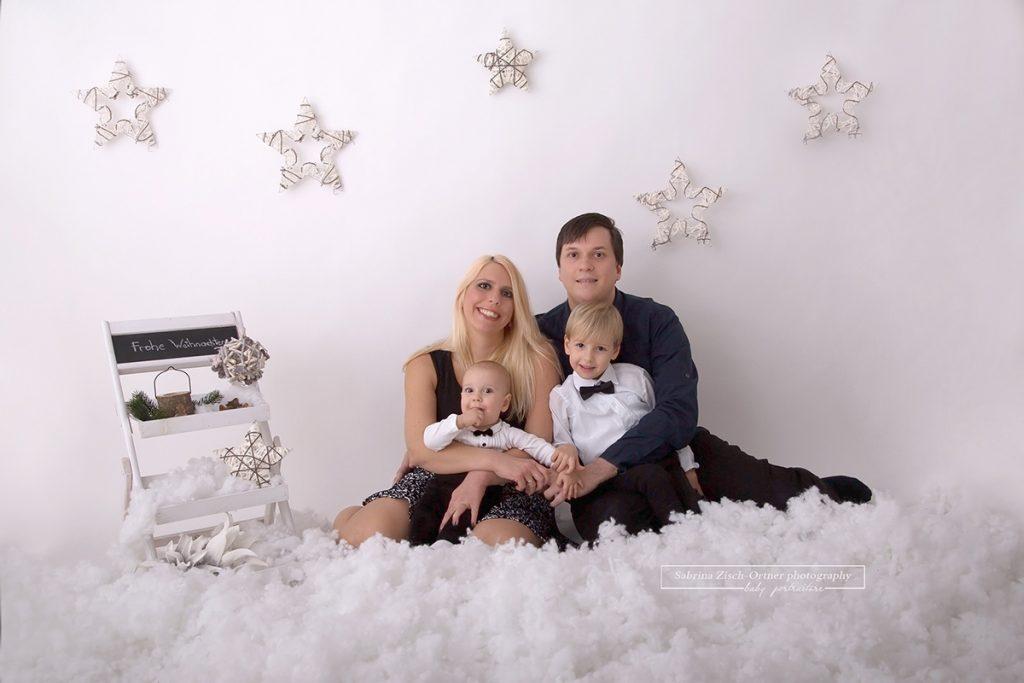 Familienfoto im weihnachtlichen Schnee Setup mit hängenden Sternen