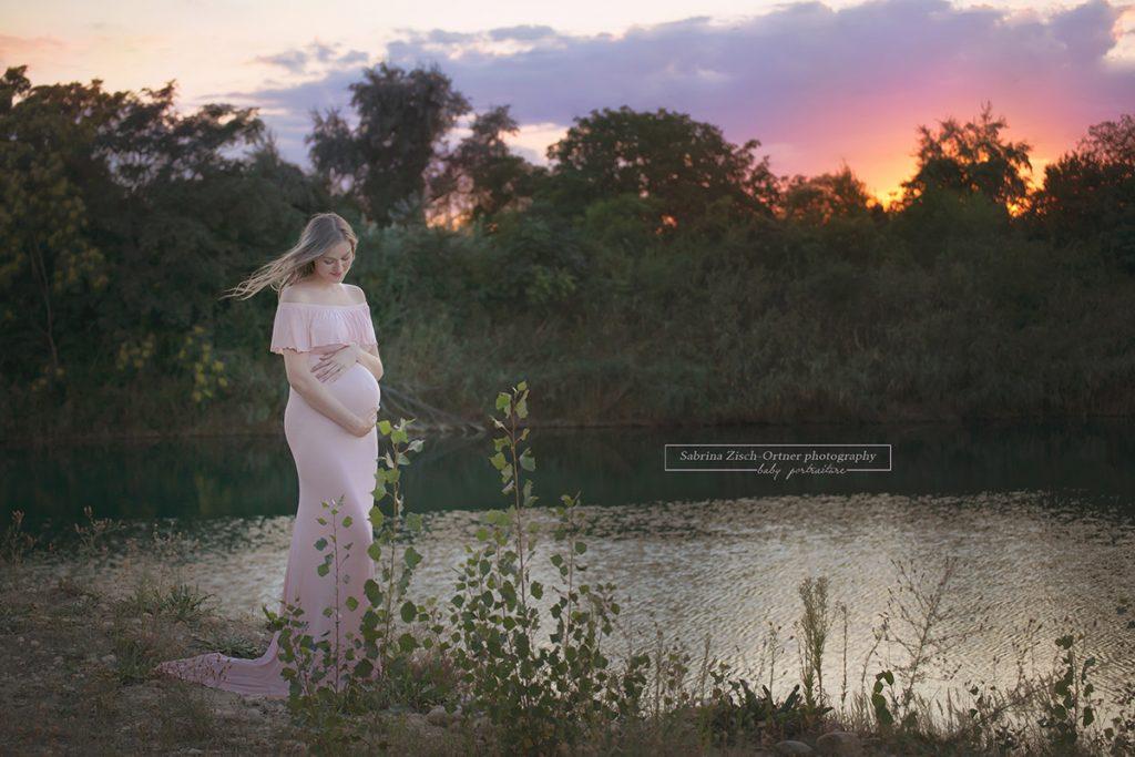 rosa Babybauchkleid vor rosa leuchtenden Abendhimmel