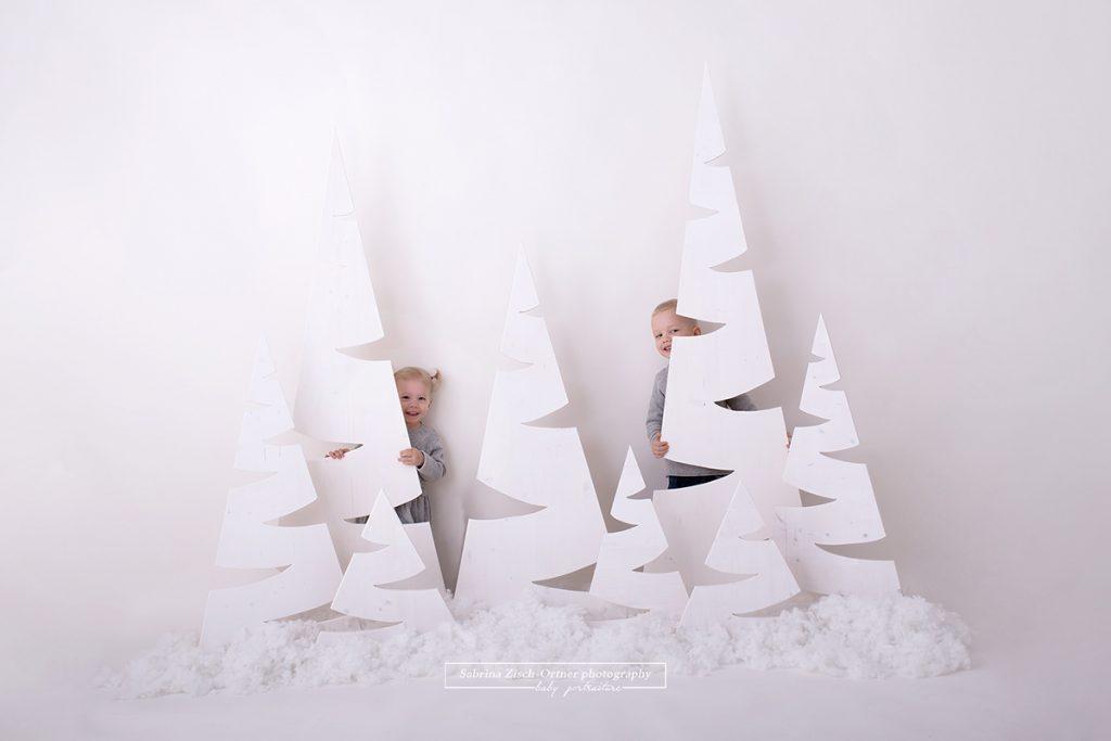 Schwester und Bruder spielen hinter den Acht Bäumen, welche von 40cm Höhe bis zu 180cm Höhe reichen, im Studio verstecken und grinsen fröhlich seitlich hervor.