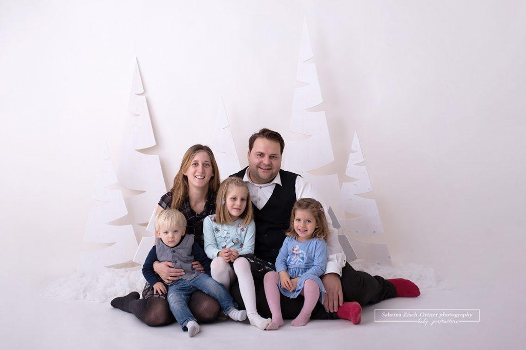 weihnachtliches sitzendes und kuschelnde Familienfoto der 5 köpfigen Familie vor meinem weihnachtlichen, in weiß gehaltenen, Setup