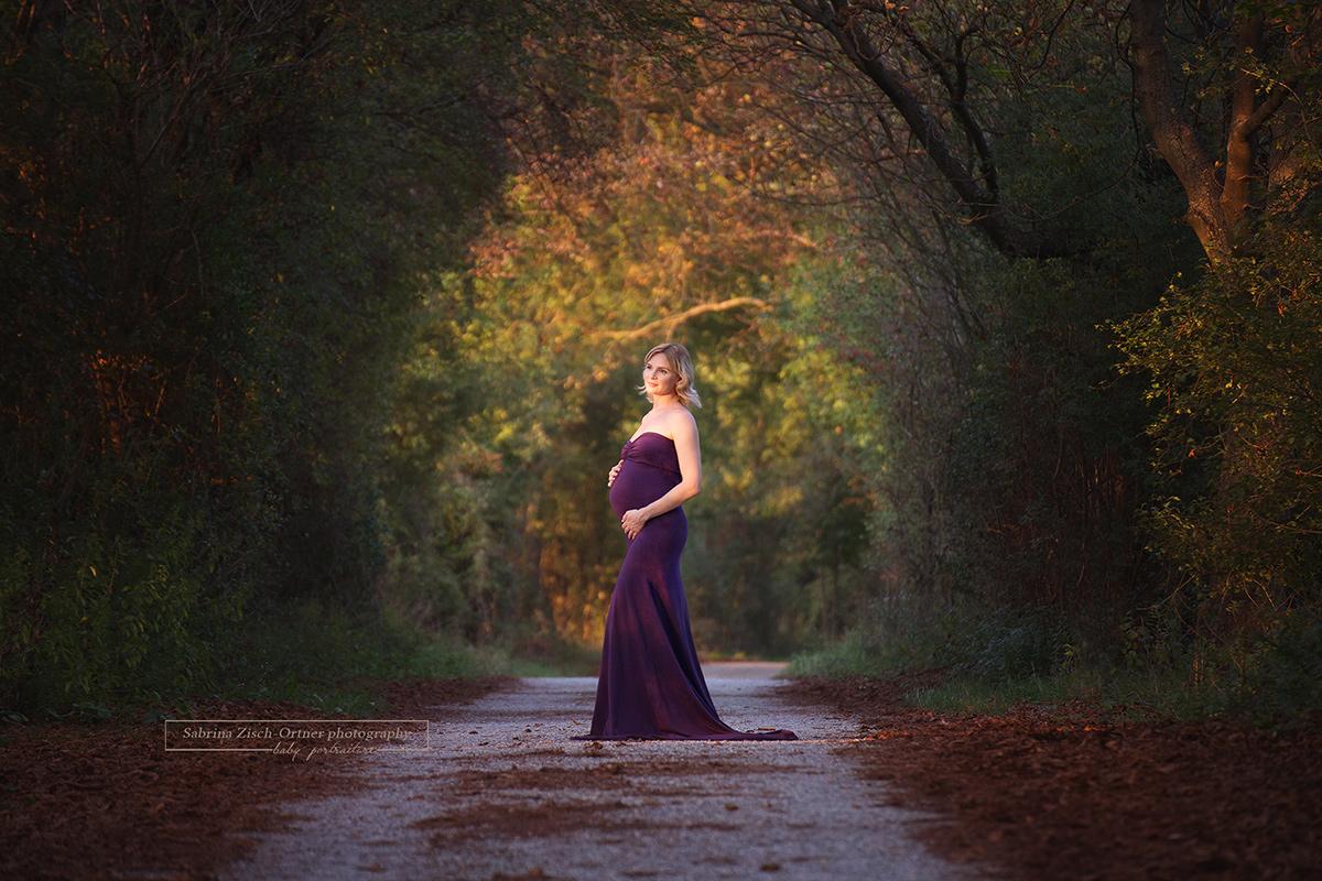 wunderhübsche Schwangere im lila Babybauchkleid im Abendlicht getränkten rotgelb schimmernden Wald stehend